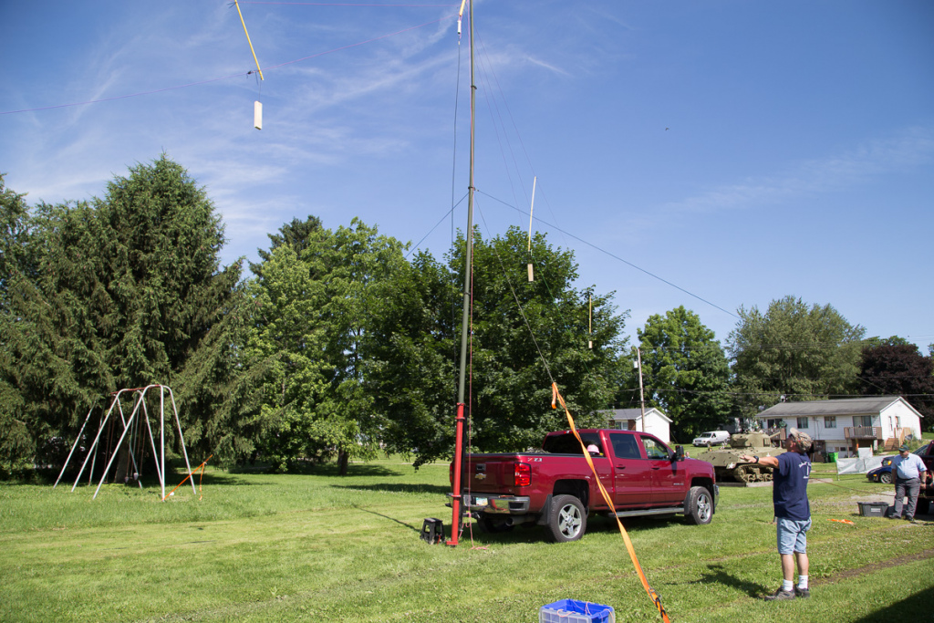 An antenna and antenna mast mounted on the back of a truck.